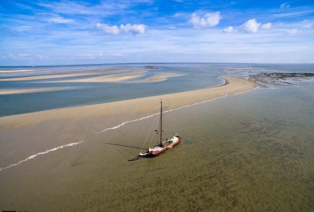 A flat-bottomed ship in the middle of the Waddensea area