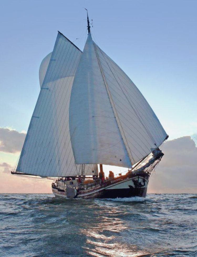 Zeilschip de Waterwolf met ruim 1000 vierkante meter zeil gehesen, op weg naar de Waddeneiland tijdens een zomerse zeilvakantie