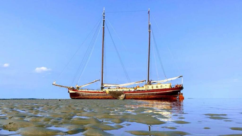 Zeilschip de Waterwolf tijdens het droogvallen op het Wad