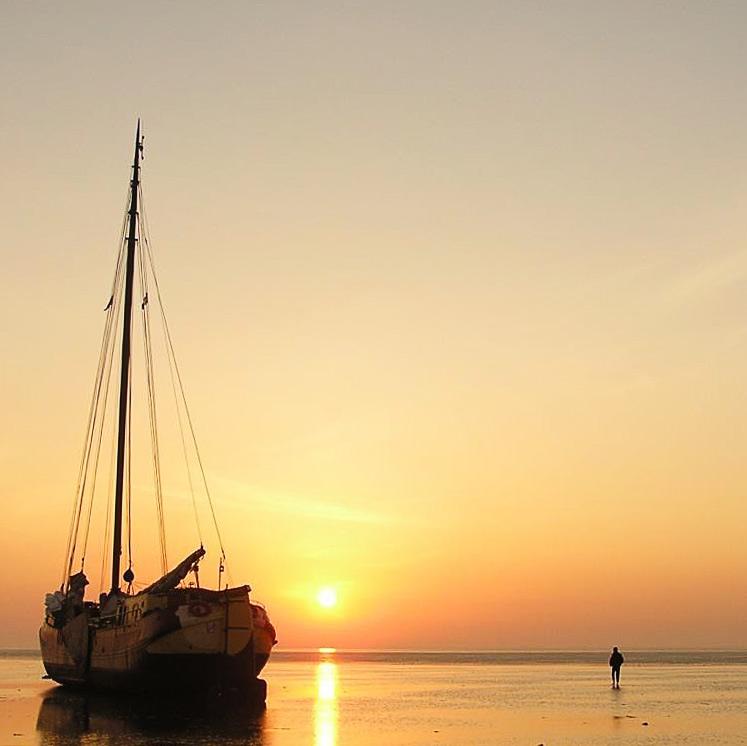 Zeilschip de Lotus in de zonsondergang op het Nederlandse Wad