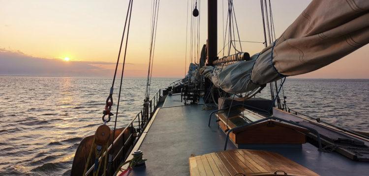 De zonsondergang tegenmoet varen in Nederland