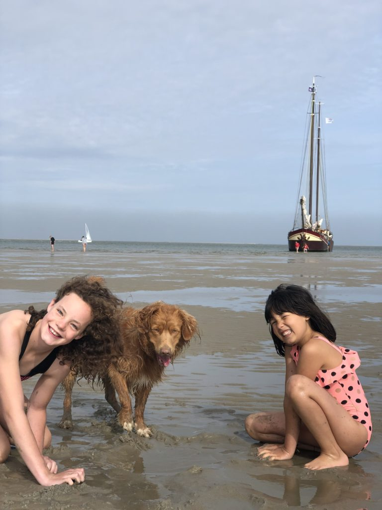 Spelen op de het strand, tijdens het droogvallen met een authentieke platbodem