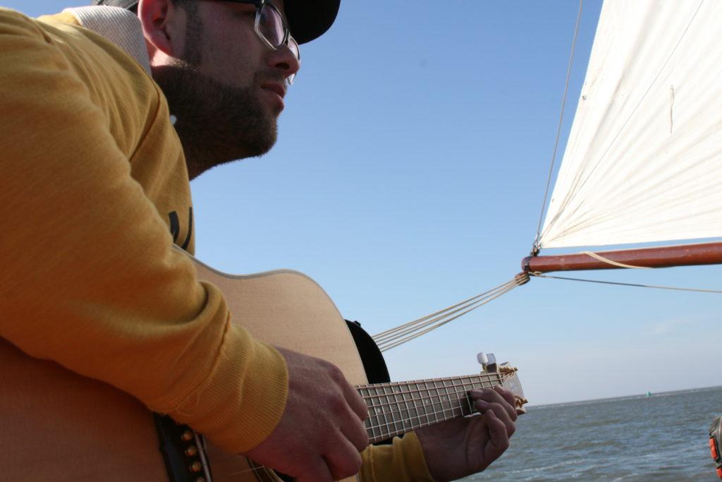 Blues muzikant treden op onderweg naar Terschelling op een authentiek zeilschip