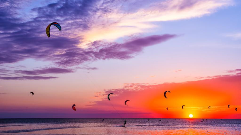 Kiters in Nederland bij een rode zonsondergang.